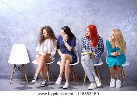 Young girls sitting on a chairs and looking at the empty place in grey hall
