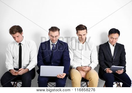 Young businessmen sitting on a chair and using devices in white hall