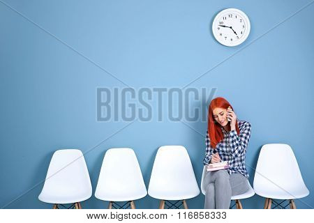 Young redhead girl sitting on a chair and talking on mobile phone in blue hall