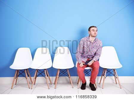 Young man sitting on a chair in blue hall