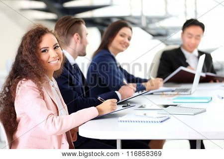 Young businesswoman with curly hair sitting at the office meeting