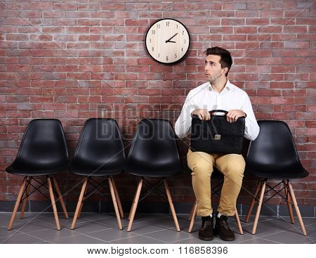 Young businessman sitting on a chair in brick wall hall