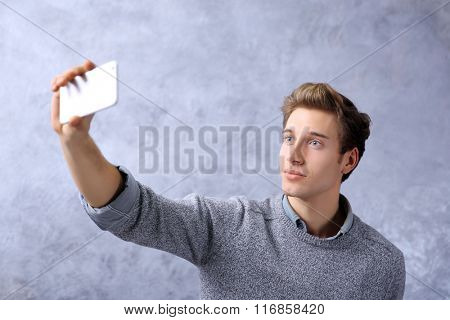 Young boy taking photo of him self with smart phone on grey wall background