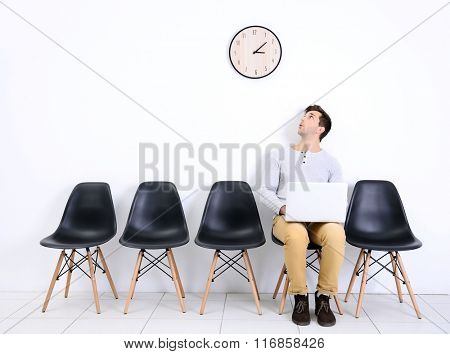 Young man sitting on a chair and looking at the clock in white hall