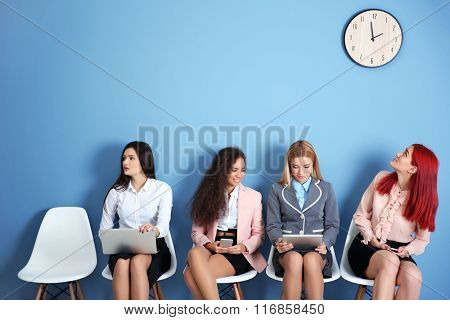 Young businesswomen waiting, sitting on a chairs and using devices in blue hall