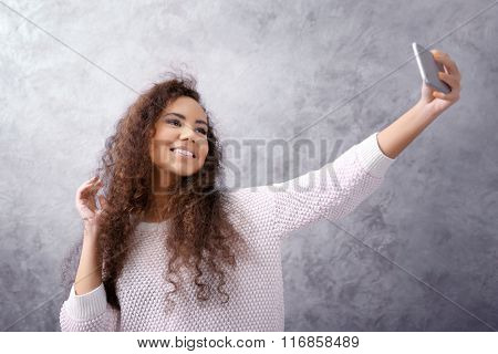 Young girl with curly hair taking photo of her self on grey wall background