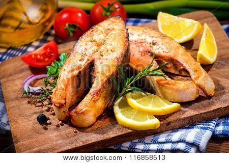 Grilled salmon steaks with vegetables on cutting board