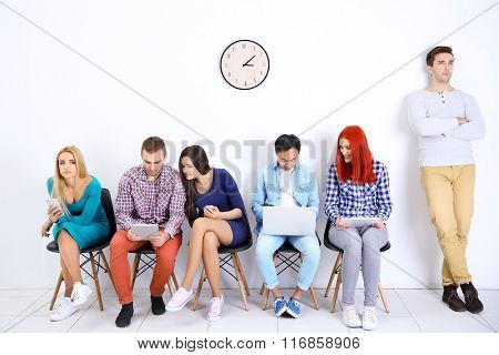 Young people sitting on a chairs and using devices in white hall