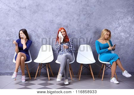 Young girls sitting on a chairs in grey hall