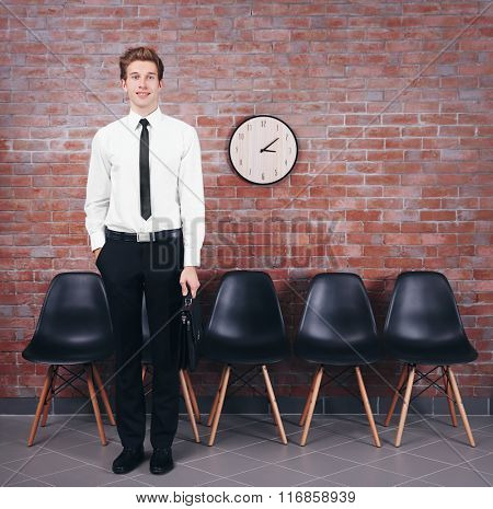 Young businessman standing in brick wall hall
