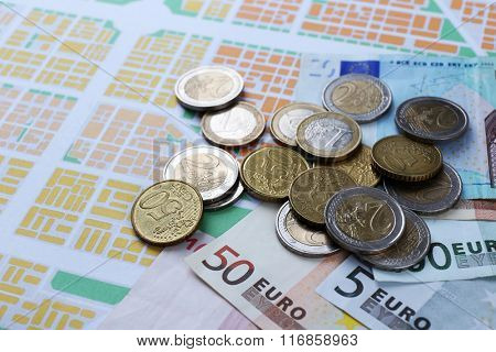 Euro coins and banknotes on map background
