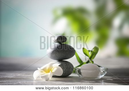 Spa stones with tropical flower, bamboo and candle on blurred background