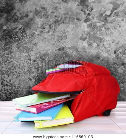 School backpack on wooden desk, on grey abstract background