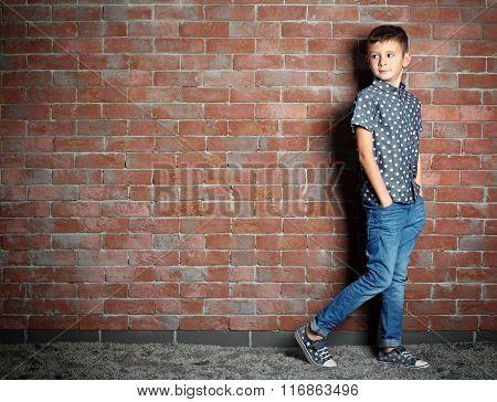Cute little boy on brick wall background. Kids fashion concept