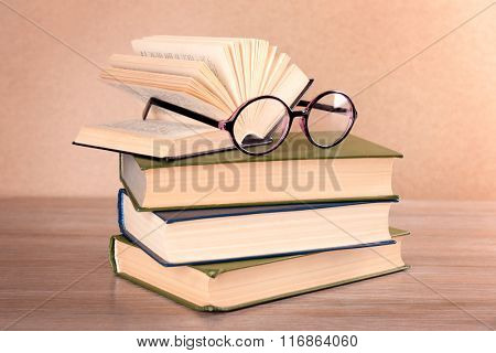 Pile of books and eyeglasses on it on wooden table, close up
