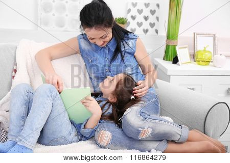 Mother and daughter reading book on the sofa