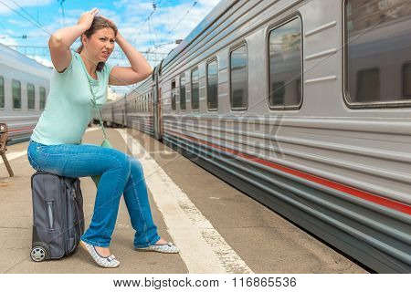 Frustrated Woman Looking At The Passing Train On Which She Was Late