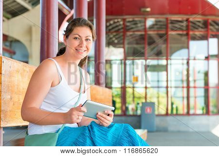 Smiling Girl With The Tablet On The Bench Waiting For Transport