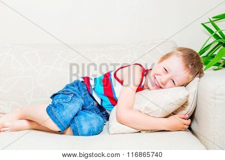 Portrait Of A Laughing Little Boy On The Sofa With A Pillow