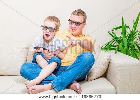 Father And Son In 3D Glasses Watching Tv On The Couch