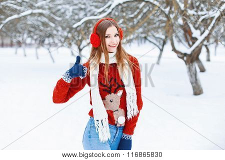 Young Beautiful Girl In A Red Sweater With A Reindeer And Winter Headphones To Have Fun In The Park.
