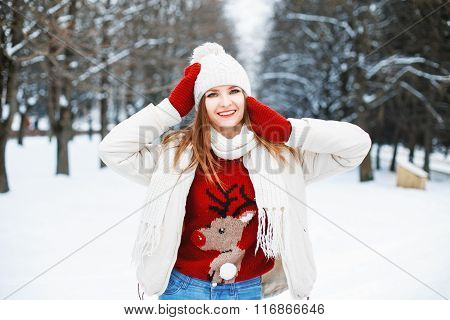 Girl In Stylish Winter Clothes Resting In A Park On A Background Of Trees