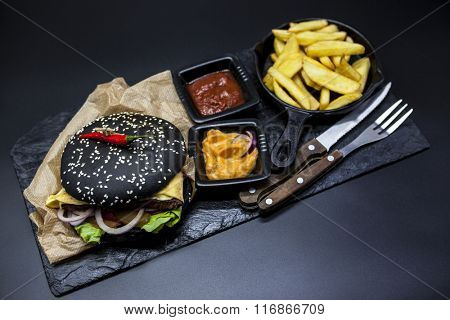 Black burger. Set of the black burger. Stone plate with: black burger roll slices of   marble beef, fused cheese, fresh salad with French fries on a cast-iron griddle, with chili sauce and guakomole.