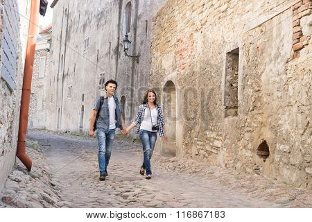 Young travelling couple having a medieval walk on an old street with tile road.