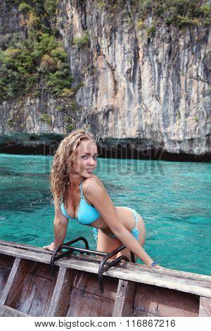 Woman in bikini on boat floating in beautiful lagoon in Thailand