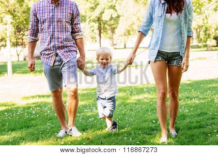 Parents having a walk with son in the summer park.