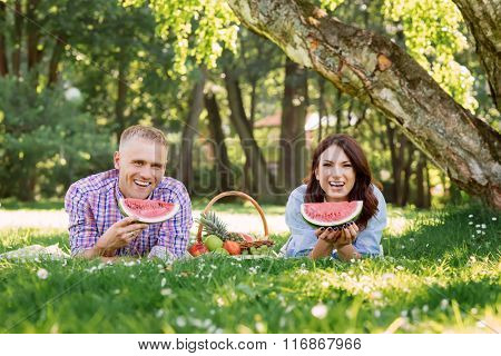 Lovely beautiful couple eating watermelon and lying on the grass in the summer park.