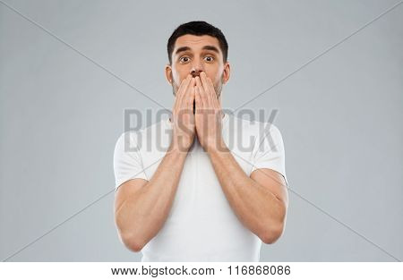 scared man in white t-shirt over gray background