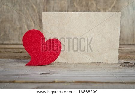 Red Fabric Heart With Sheet Of Paper Standing On A Wooden Board. On Old Wood Background.