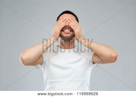 smiling man closing his eyes over gray background