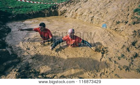 Runners crossing mud pit in a test of extreme obstacle race