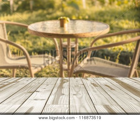 Wood Table And Blurry Chairs For Relax In Garden.