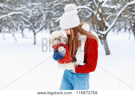 Young Beautiful Girl In A Warm Winter Clothes Plays With A Puppy In Her Arms In The Park.