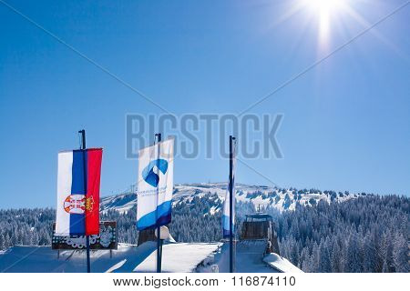 Serbian and ski resort flags on snowy mountain background and sun