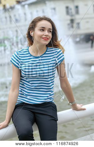 Student In A Striped T-shirt Is Listening To Music