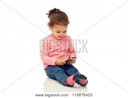 smiling little baby girl playing with smartphone
