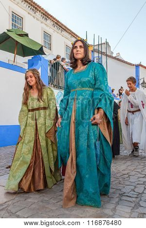 Obidos, Portugal - August 09, 2015: Noble ladies in the parade of the Medieval Market reenactment. The Medieval Market festival is very popular among tourists.