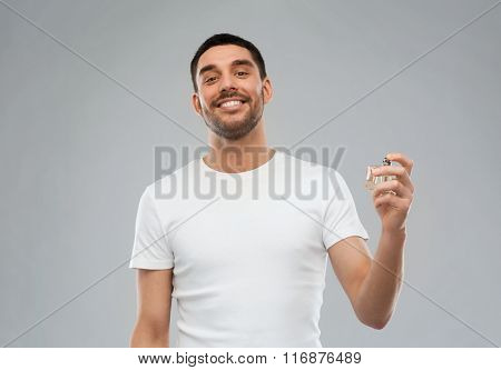 smiling man with male perfume over gray background