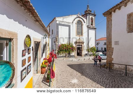 Obidos, Portugal - August, 2015: Sao Pedro church and a souvenir shop. Obidos is a medieval town inside walls, and very popular among tourists.