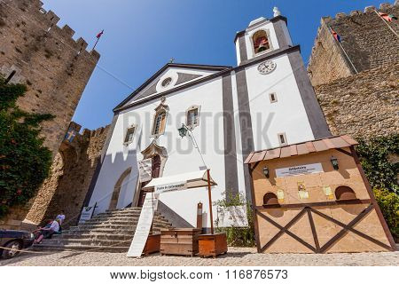 Obidos, Portugal - August, 2015: Santiago Church and Albarra Castle Tower. Obidos is a medieval town still inside castle walls, and very popular among tourists.