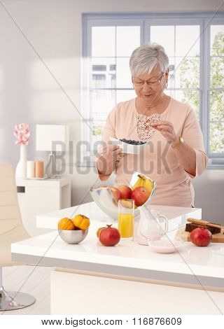 Old woman eating blueberry, many fruits on kitchen counter.