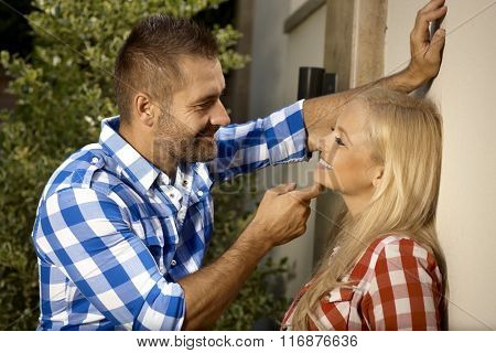 Happy handsome stubbly man, leaning against wall, flirting with young blonde woman outdoor, smiling.