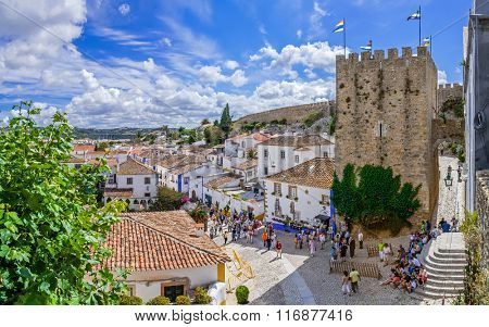 Obidos, Portugal - July, 2015: Cityscape of the town with medieval houses, wall and the Albarra tower. Obidos is a medieval town still inside castle walls, and very popular among tourists.
