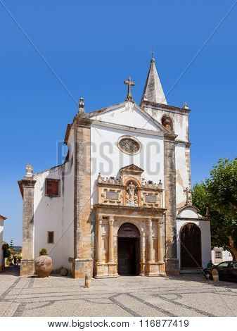 Obidos, Portugal - August, 2015: Medieval Santa Maria Church showing a Renaissance Portal. Obidos is a medieval town inside walls, and very popular among tourists.