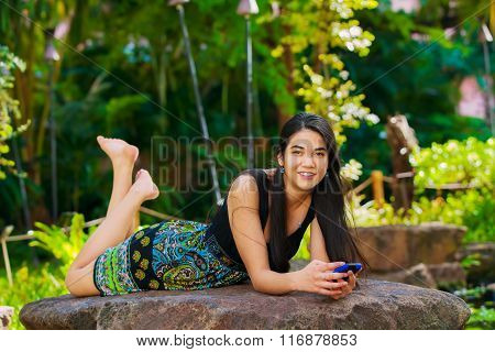 Biracial Teen Girl Lying On Rock Looking At Cellphone Outdoors