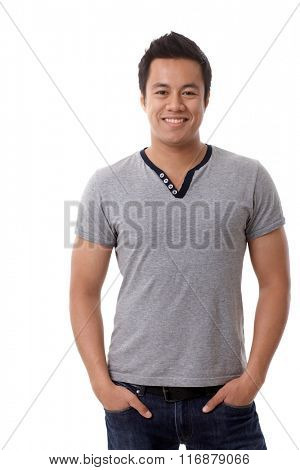 Happy young casual man standing with hands in pockets, looking at camera.
